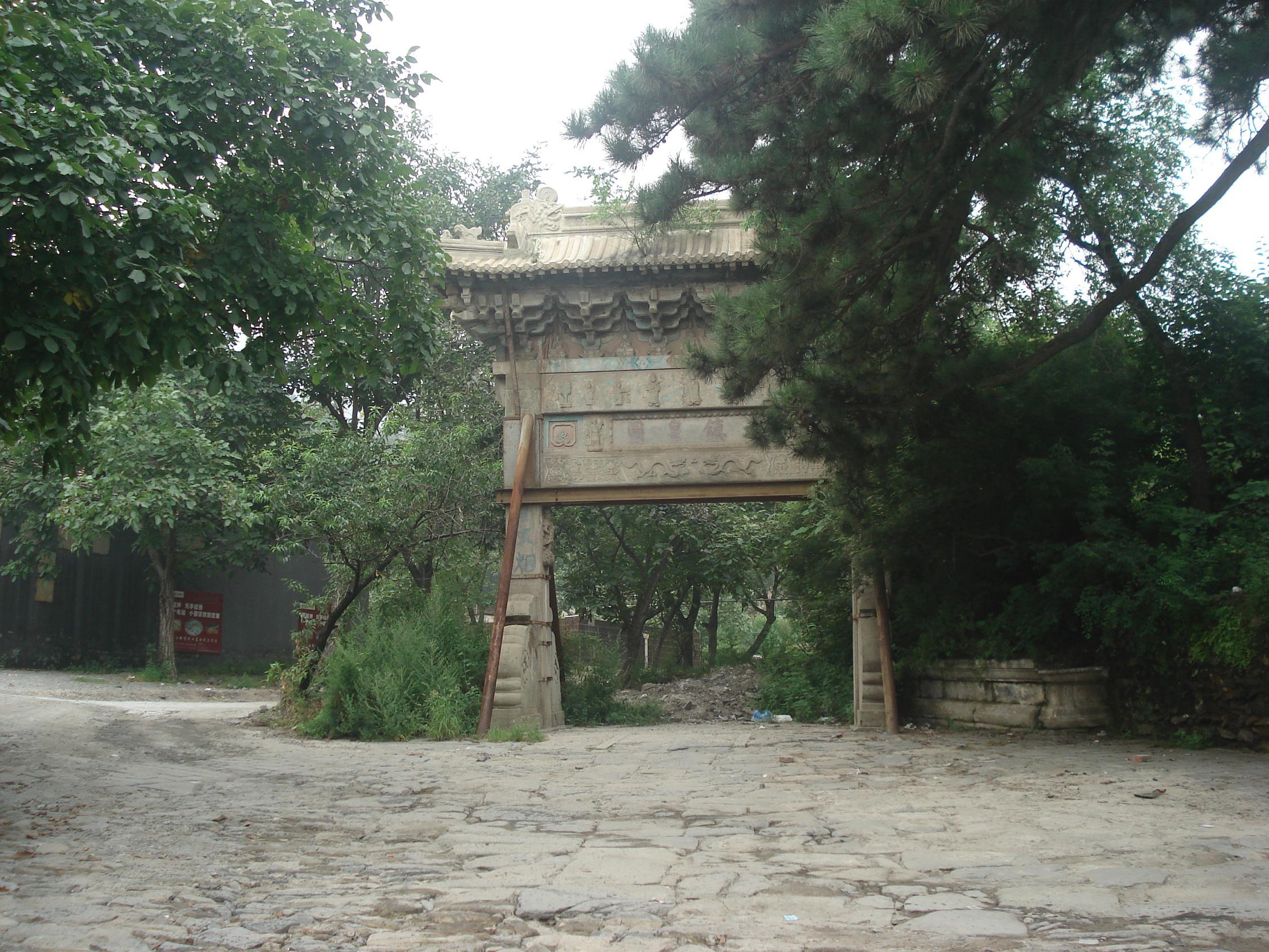 转:戒台寺石牌坊坐西朝东,与戒台寺遥相呼应,据说是北京现存最古老的牌楼了。 石牌坊采用汉白玉石料錾雕的仿木结构建筑,两柱单间一层楼,庑殿顶,其彩绘可与十三陵石牌坊的彩绘相媲美。其背面匾额为祗园真境,落款有两行小字大明万历二十七年岁次己亥季春吉日立,说明它创建于明万历27年(1599年)。正面匾额为永镇皇图,落款有几行小字大清光绪壬辰年秋季九月吉日弟子长白文麟重修说明清光绪18年(1892年)进行过重修。石牌坊两边楼柱有莲座楹联,上联是:星海空澄广映无边诸佛地,下联是:日轮皇鉴大明洪护梵王家。