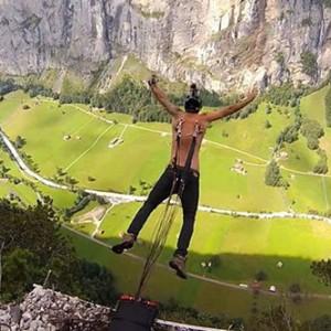 俄男子铁钩穿背玩跳伞 跳下400米悬崖